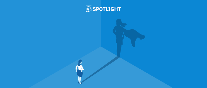 Business woman staring at her shadow on the wall which shows her wearing a cape like a super hero