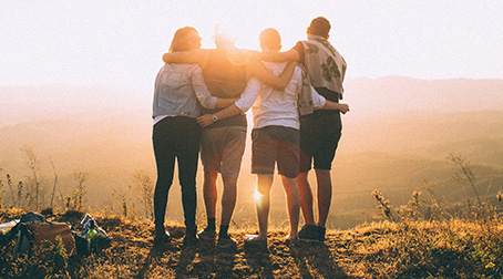 Four people with their arms around each other overlooking a sunset