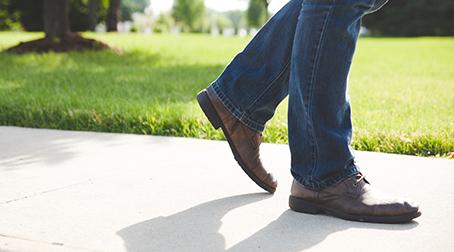 man walking on a sidewalk on a sunny day