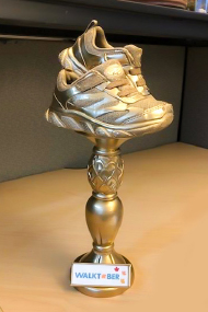 gold trophy with a shoe at the top